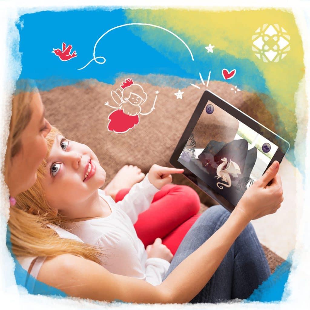 Criança no colo da mãe, que segura um tablet (telas) com o app Truth and Tales aberto numa tela. Ilustrações de passarinhos e fadas.